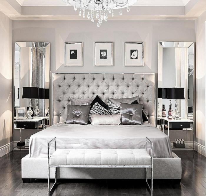 lustre en cristal, tete de lit grise capitonnée, coussins déco sur le lit, lampes abat-jour noires