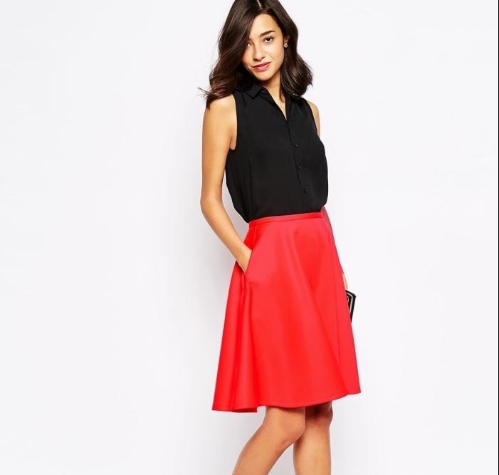 modèle de tenue décontractée chic femme en jupe rouge et chemise sans manches noires accessoirisés avec pochette noire
