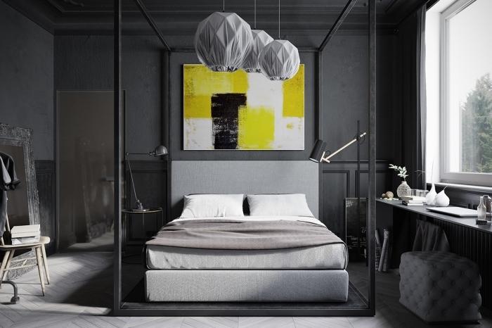 modèle de chambre adulte stylé avec peinture murale en gris foncé aménagée avec grand cadre de lit en fer noir