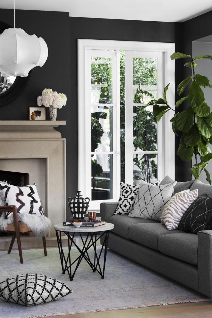 salon au plafond blanc et murs foncés avec grandes fenêtres aménagé avec meubles moderne et cheminée
