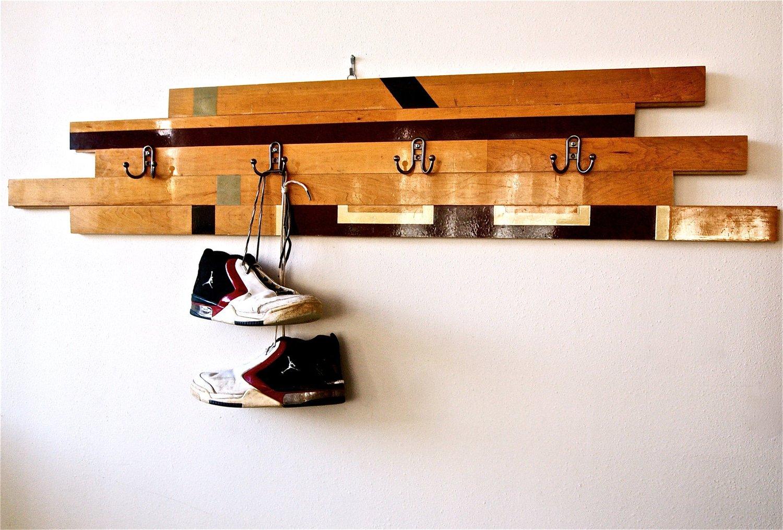 porte manteau original en lattes de bois avec des accroches metalliques noires sur un mur blanc, sneakers suspendus