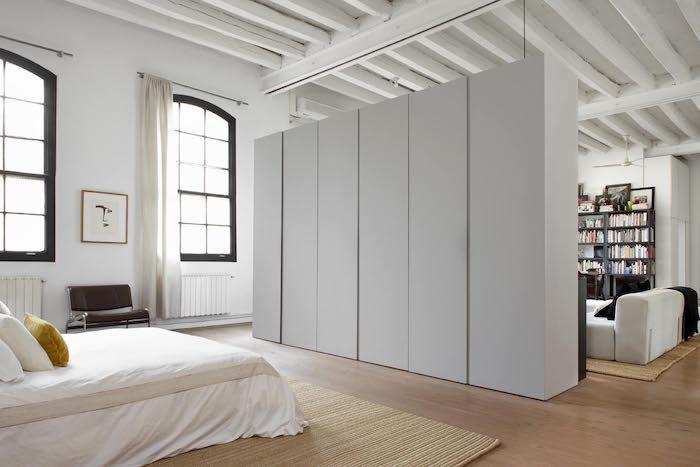 linge de lit blanc, tapis beige, armoire industrielle blanches, grandes fenêtres industrielles, parquet bois clair