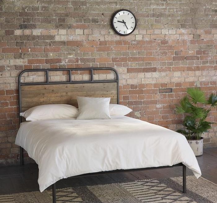 déco style industriel avec mur en briques, lit en bois et métal, linge de lit blanc, tapis gris et blanc, plante verte, petite horloge industrielle