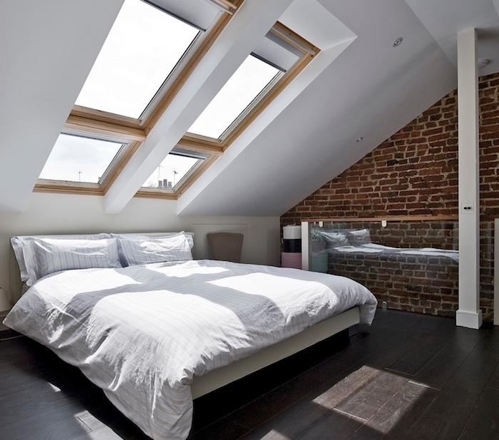 exemple d aménagement de chambre à coucher sous comble avec de grandes fenêtres, parquet bois foncé, linge d elit blanc