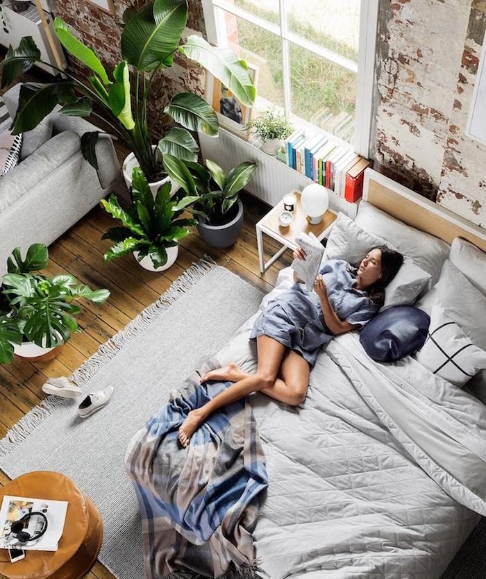 plantes vertes dans un espace loft industriel, aménagement coin chambre avec linge de lit gris et mur defraichi, parquet bois clair, tapis gris