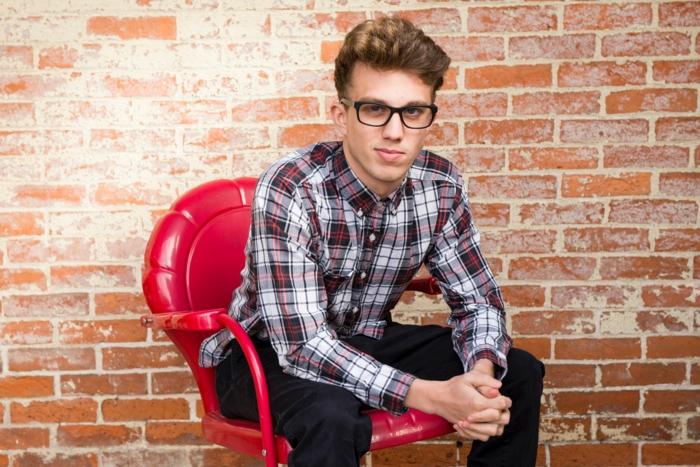 jeune homme avec monture tendance pour le 2018, lunette hipster, grosse lunette de vue, homme assis sur une chaise en plastique rouge