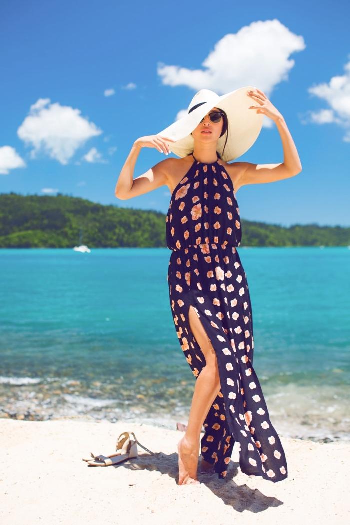 modèle de robe femme ete longue et bleu marine avec fleurs rose, accessoires plage avec capeline et lunettes de soleil