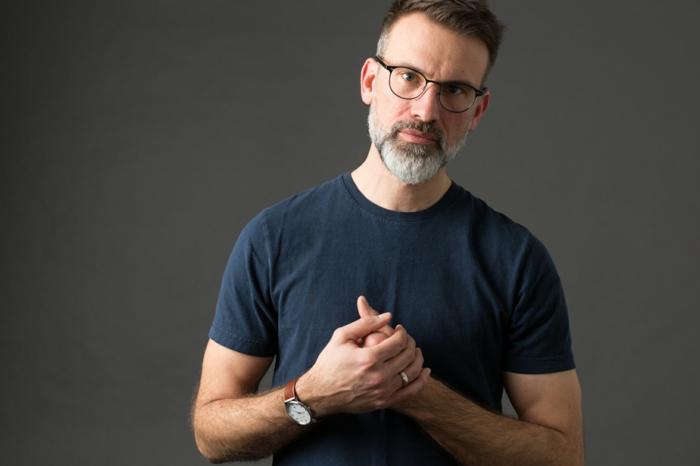lunette homme aux lignes pures et fines en noir, lunette de vue tendance, lunette hipster, homme avec T-shirt en bleu marine et barbe grise
