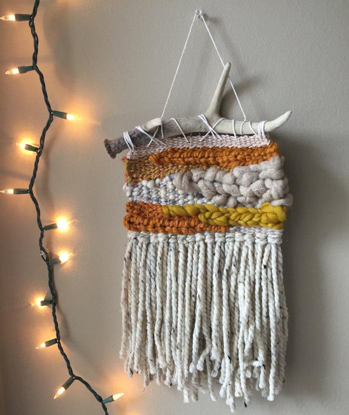 tissage deco macrame en laine avec bois flotté sur mur gris