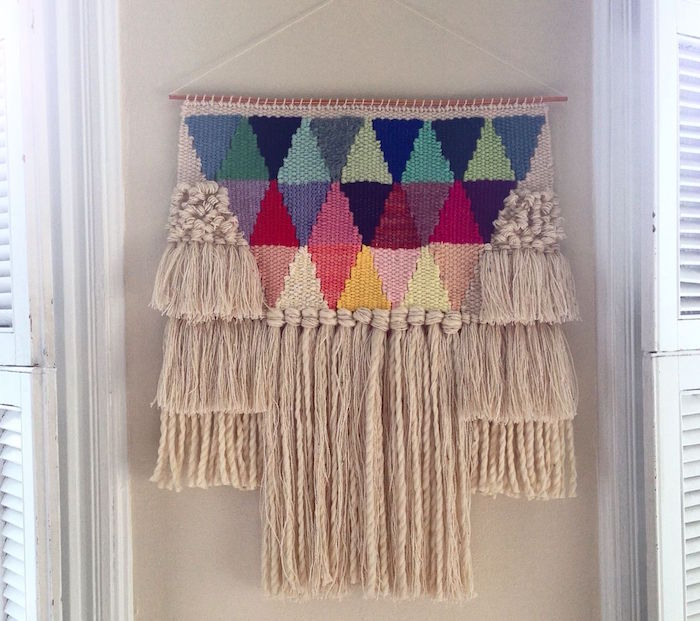 modele de macramé mural tissé avec triangles en couleurs et frange de laine beige