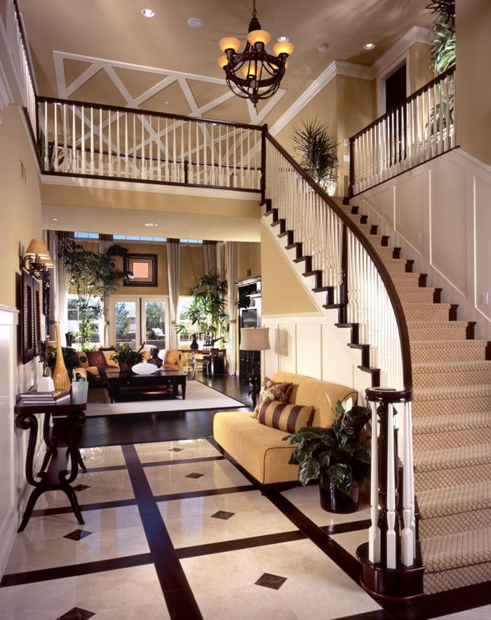 créer une décoration d'entrée chic dans une maison de luxe, grand escalier, console en bois, carrelage en noir et blanc, sofa beige, créer une entrée dans un espace ouvert
