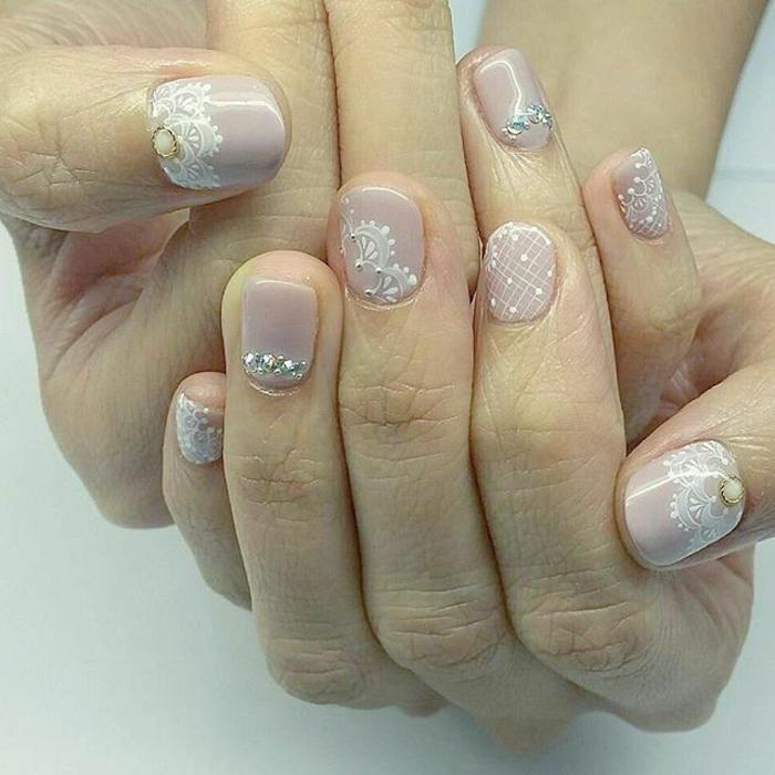 manucure lilas pale, jolies décorations blanches sur ongles très courts et strass métallique