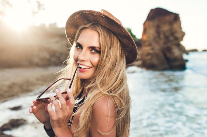 idée quels bijoux et accessoires porter sur la plage avec bagues de style hippie et capeline marron, cheveux longs aux mèches blondes
