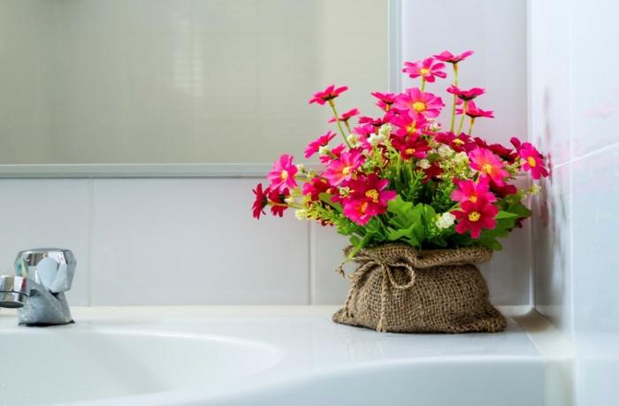 plante salle de bain sans lumière, fleurs en couleur fuchsia, pot habillé de sacoche en toile brodée, plante interieur ombre, coin de lavabo blanc décoré de fleurs