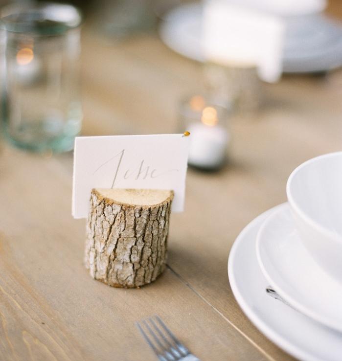petit buche de bois avec fente pour insérer une etiquette mariage blanche, sur une table bois brut, vaisselle blanche