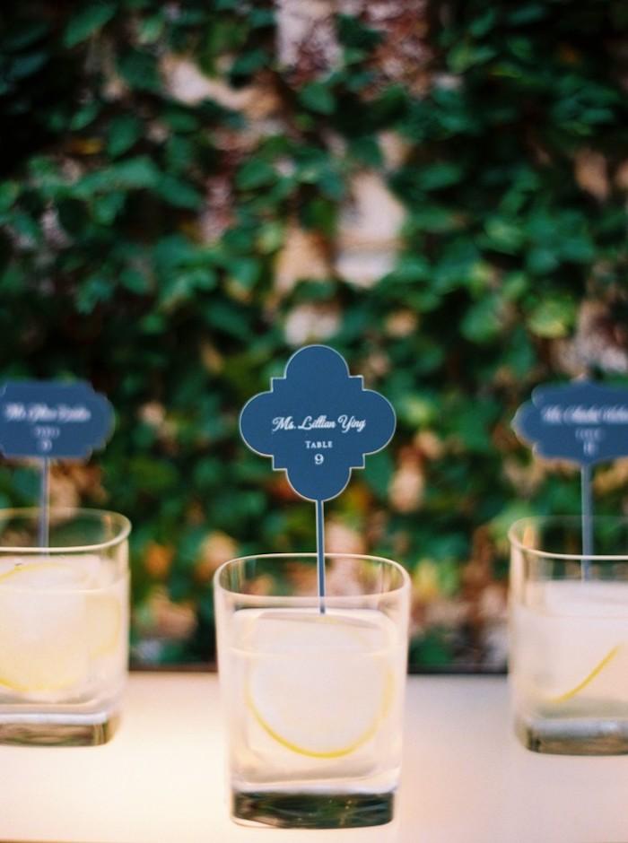exemple de marque place apéritif avec le prénom invité et le numéro de la table écrits sur une tablette peinture tableau noir