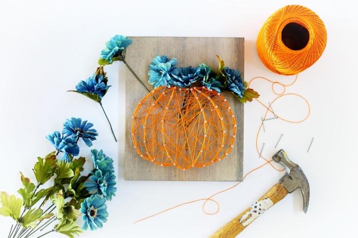 idée bricolage de Halloween avec planche de bois joliment décorée en fil tendu orange et fleurs artificielles bleues en forme de citrouille