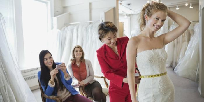 préparation de la mariée, le spécialiste styliste mesure la taille pour la robe, robe de mariée bustier, robe de mariée sirène, robe de mariée près du corps