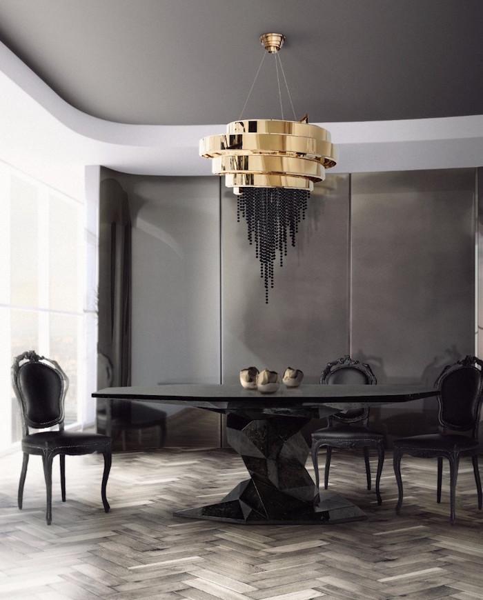 Salle à manger luxe style art moderne avec table noire design et lustre or dans décoration gris anthracite
