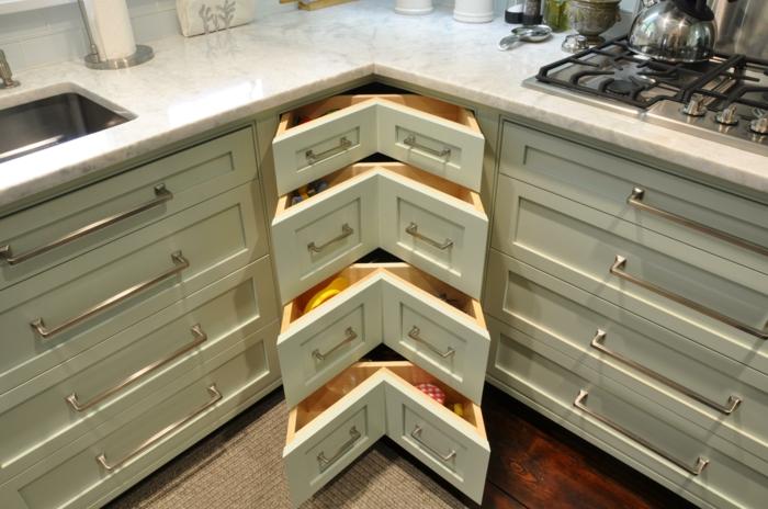 meuble angle cuisine en vert pistache, petits tiroirs en angle, plan de surface aux effets marbrés blanc et noir, rangement placard cuisine