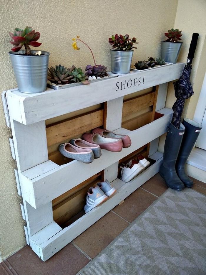un meuble chaussure palette fonctionnel avec des pots de fleurs intégrés pour un aménagement d'entrée d'esprit récup