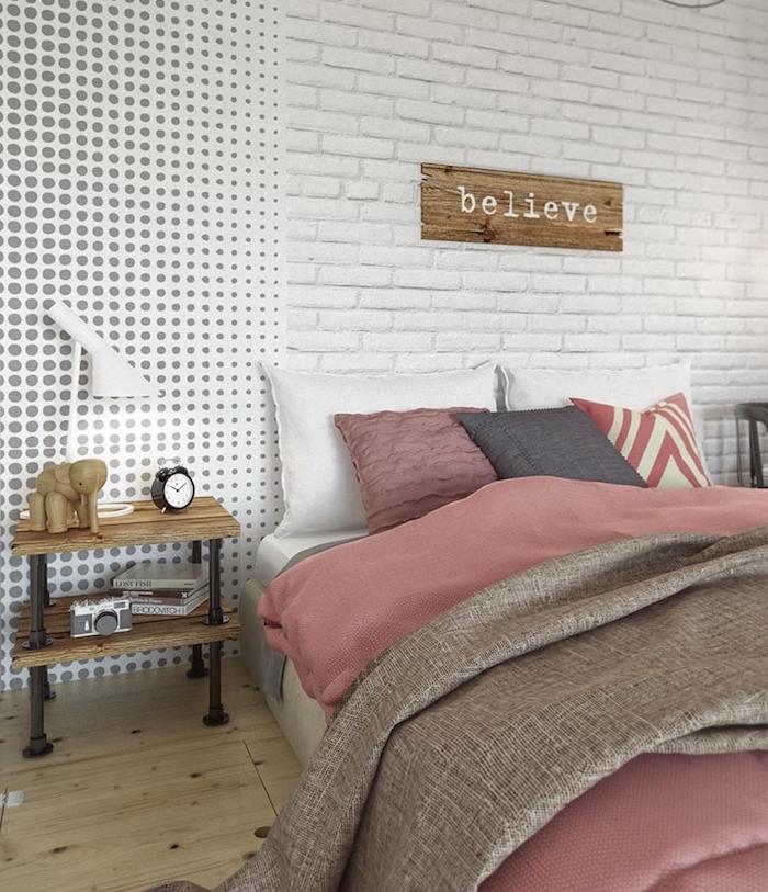 mur de briques blanches, linge de lit gris, rose et blanc, parquet clair, table de nuit bois et tuyaux en métal