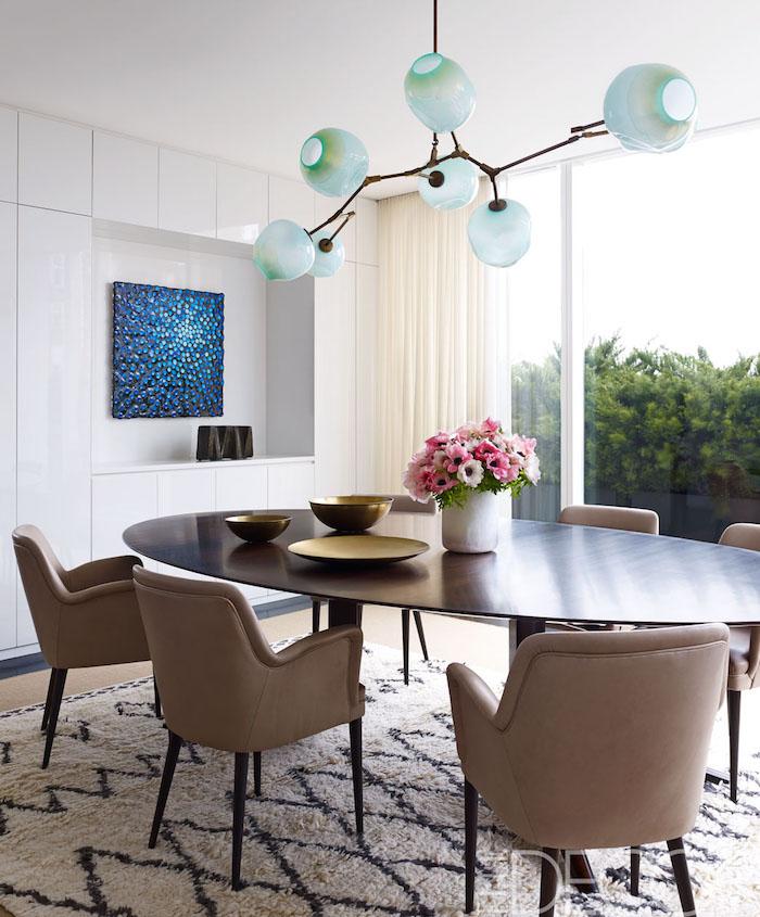 photo table à manger scandinave ovale en bois style rétro avec fauteuils vintage marron sur tapis et lustre design en verre soufflé