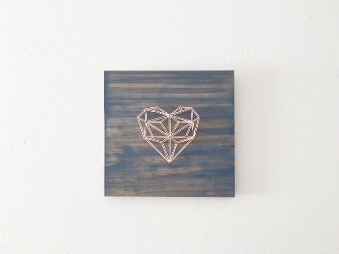 exemple de décoration murale dans le style minimaliste avec un coeur origami en fil blanc et rouge sur une planche de bois