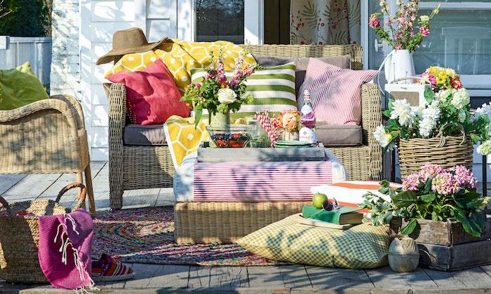 amenagement petite terrasse exterieur en bois naturel avec canapé et chaise rotin, coussins colorés et tapis tressé coloré, plusieurs bouquets de fleurs