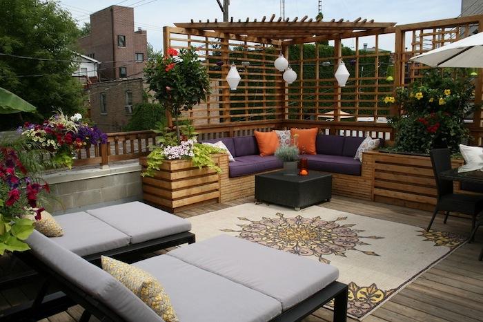 amenager une terrasse exterieure en bois, chaise longues, canapé bois avec une pergola bois, coussins d assise violets, fleurs en pots et bacs à fleurs
