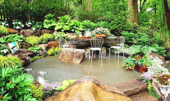 aménagement de jardin terrasse extérieure en pierre, rocaille fleurie, table en pierre naturelle et chaises metalliques, coin repas exterieur