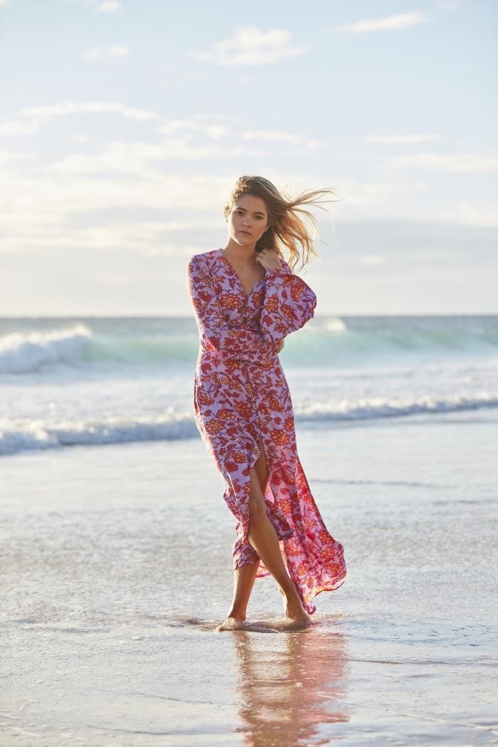 jeune femme sur plage habillée en robe légère été avec manches longues à design asymétrique aux couleurs rouge et rose