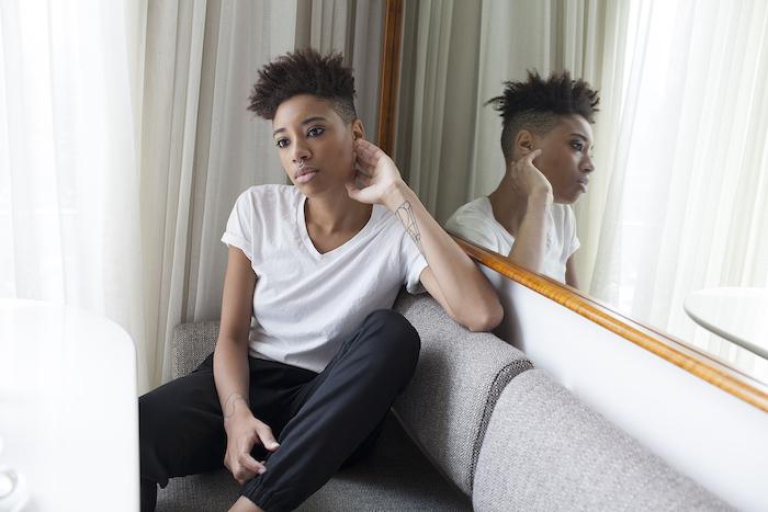 coupe courte afro femme côtés rasés et dessus en mèches longs de cheveux crépus, tee shirt blanc et pantalon noir
