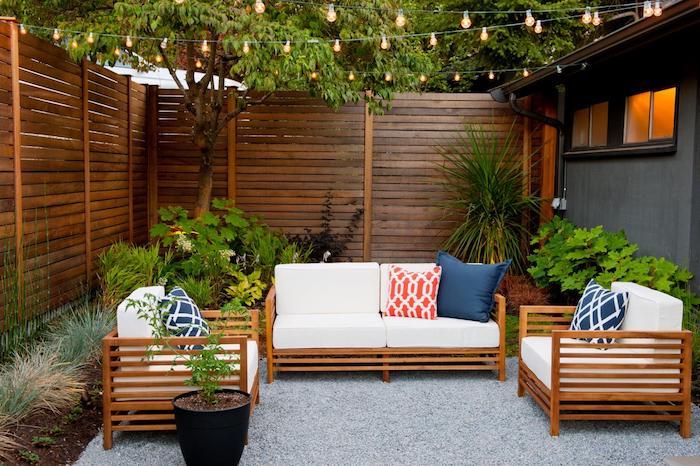 aménagement cour extérieur avec salon de jardin bois composé de fauteuils et canapé bois, revêtement sol en gravier, clôture bois composite, guirlande lumineuse