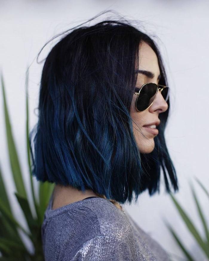 coupe au carré plongeant aux mèches bleues et racines de cheveux noires, luenttes de soleil aviateur