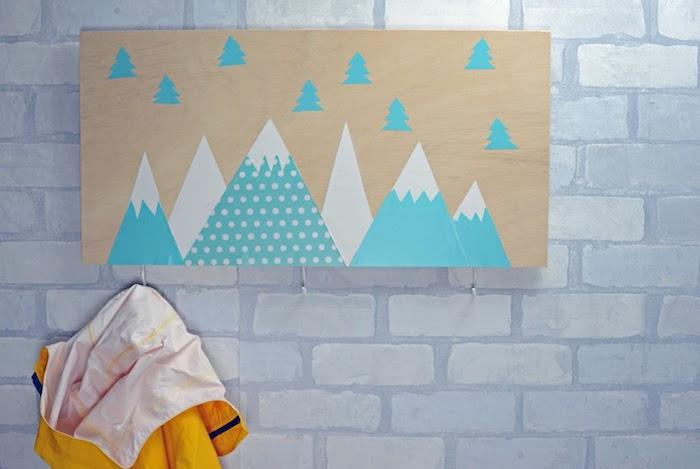 modele de porte manteau scandinave en planche de bois avec motif montagnes et sapins enneigés, mur de briques blanches, accroches simples