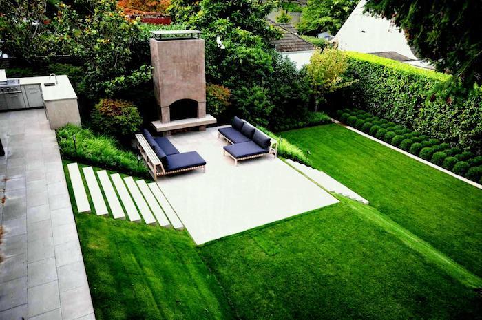 terrasse en pente avec un coin repos en canapés avec cheminée et cuisine exterieure sur le niveau supérieur