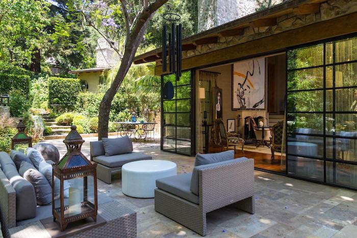 amenagement terrasse jardin exotique en canapés rotin, table basse ronde, lanterne bougie, salon séparé par une verrière noire, jardin oriental de plusieurs arbustes, buis et arbres