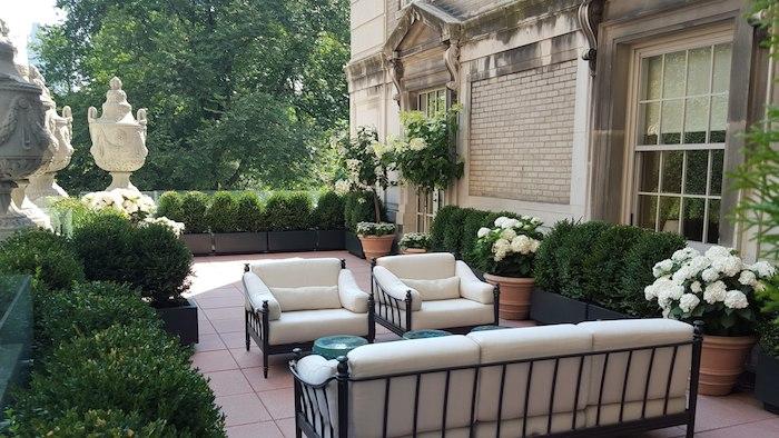 exemple aménagement de jardin terrasse en carrelage, canapé et chaises metalliques avec coussins blancs, buis taillés, art vintage, maison vintage