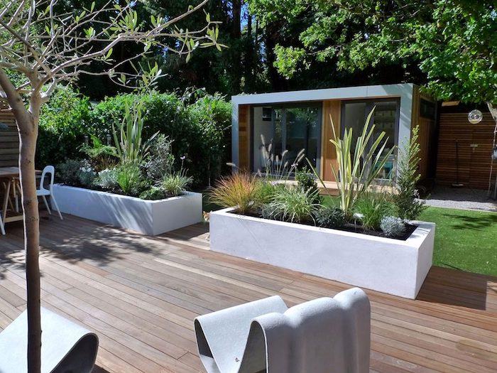 terrasse maison en bois composite, bacs à fleurs en béton blancs, fauteuils extérieur forme intéressante