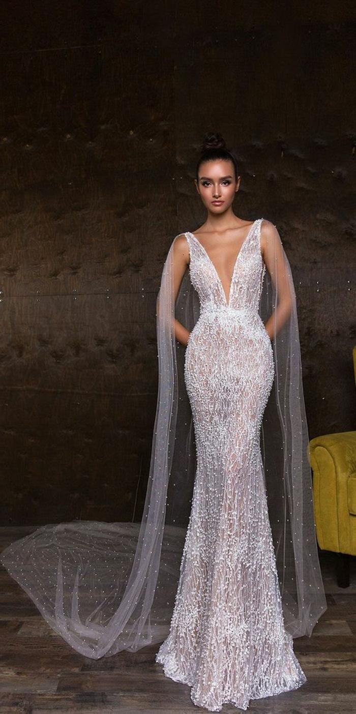 robe de mariée moulante avec des motifs scintillants sur toute la longueur, décolleté grand ouvert en V, cape traîne transparente très longue