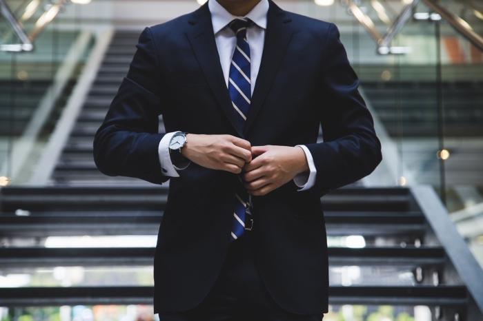 look homme élégant avec tailleur raffinée en bleu marine et chemise blanche accessoirisés avec cravate bleu marine rayée