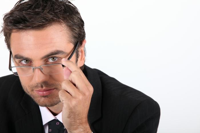 lunette transparente homme, monsieur avec costume noir, chemise blanche et cravate noire avec des carrés en jaune, allure qui met en confiance, monture de lunette tendance