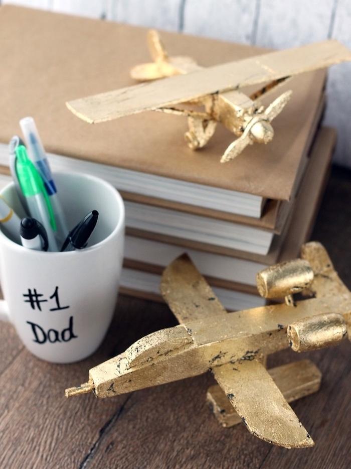 comment fabriquer un mug personnalisé avec texte papa numéro un écrit au feutre noir, pile de livres, petits avions figurines dorées, cadeau fete des peres a fabriquer, pot a crayon diy