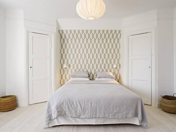 une chambre à coucher à déco épuré où la niche murale derrière le lit est mise en valeur par une tête de lit graphique en teintes neutres