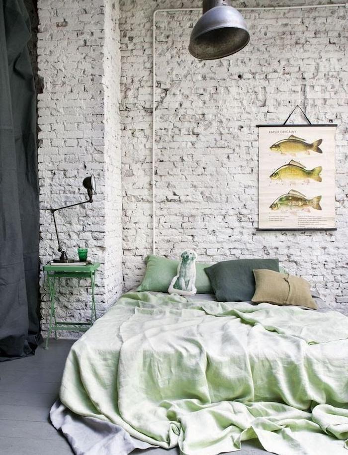 exemple de déco mur de briques blanc, linge de lit vert, sol parquet peinture grise, suspension grise originale