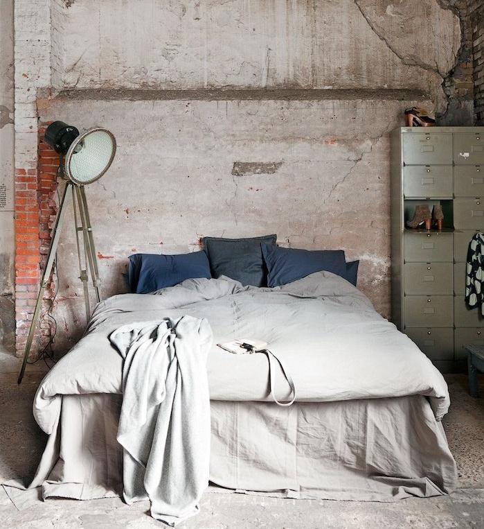 modele de casier industriel style brut avec des murs defraichis, linge de lit gris et coussins bleus, lampe industrielle originale