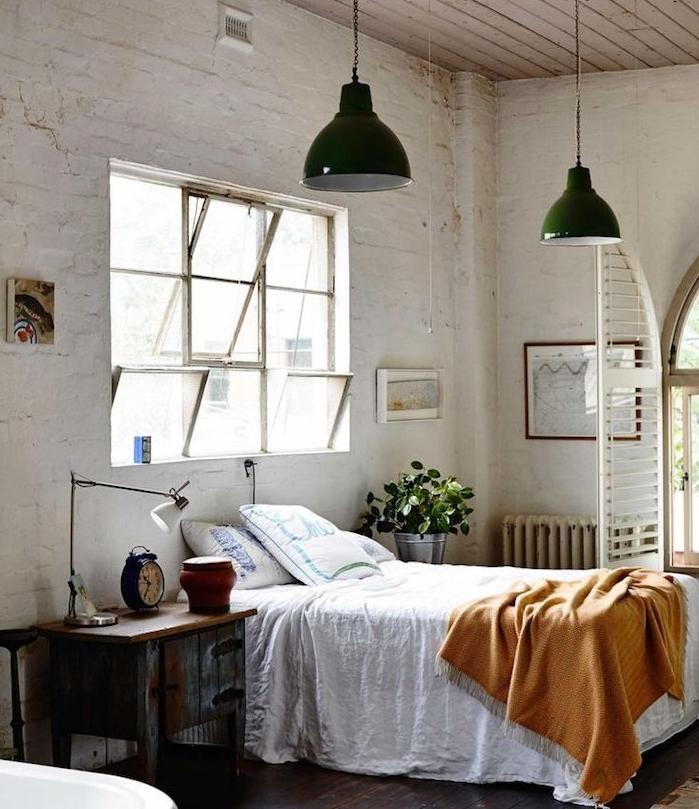 mur de briques blanc, suspensions vertes industrielles, linge de lit blanc et couverture de lit orange, parquet marron foncé, table de nuit originale bois defraicho, grandes fenetres
