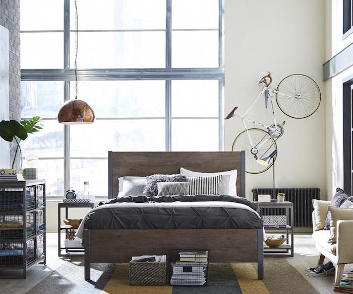 vélo comme deco murale industrielle, lit en bois et métal, linge de lit gris et blanc, tapis gris, jaune et marron, rangement casier style industriel