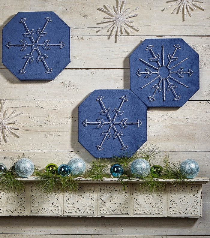 activité manuelle maternelle pour faire une décoration de Noel murale, tableau peint en bleu foncé avec flocon de neige en fil blanc